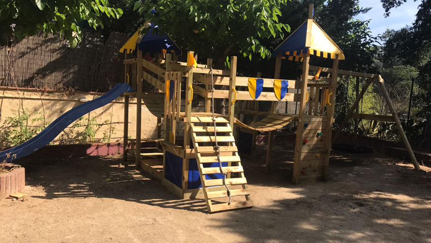 Kidszone playing castle with slide, swings etc in the garden